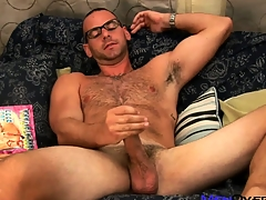 Hot bear yon glasses plays with his cock while leafing through a gay porn mag